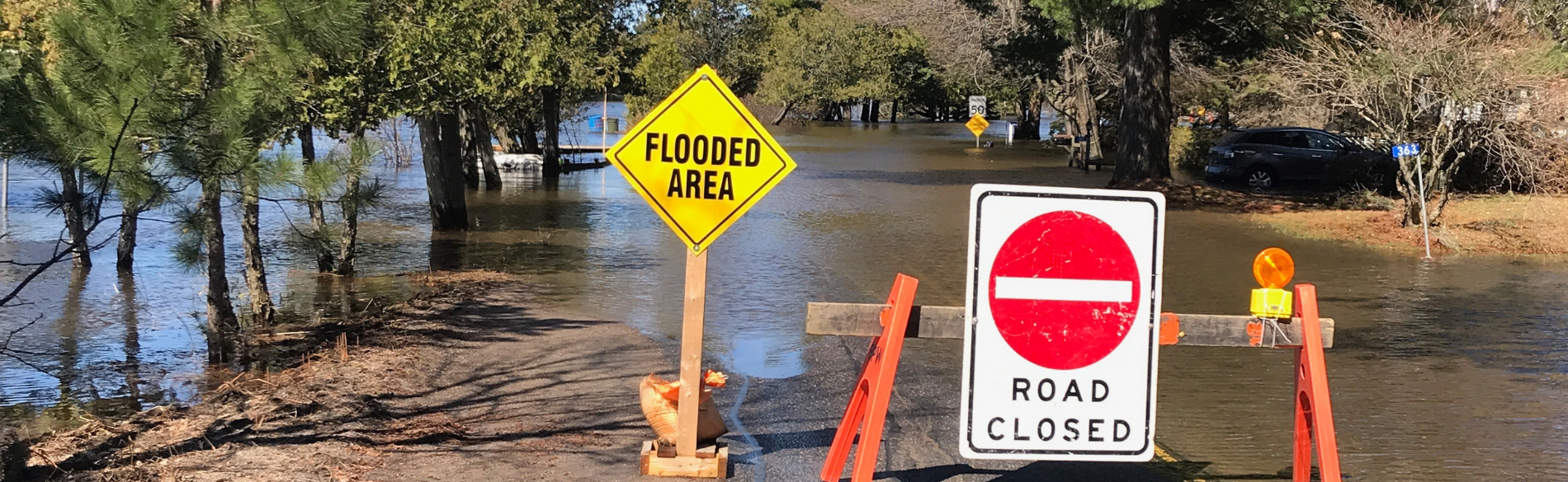 "a flooded road with a road closed sign across it and another sign that reads ""flooded areas"""