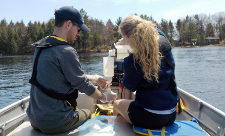 Two people in a boat pouring water into sampling equipment