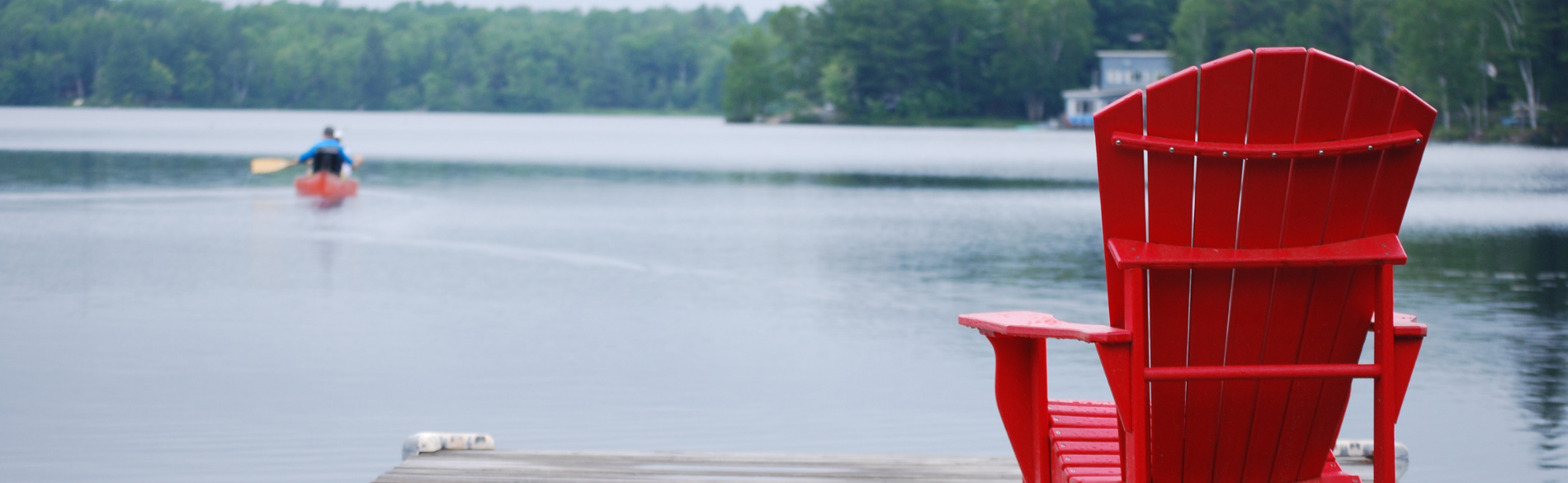 empty red muskoka chair on a dock facing a lake