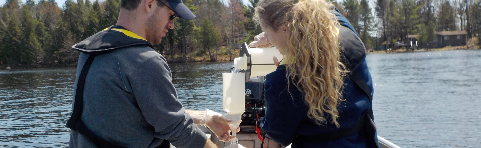 two summer students conducting water sampling