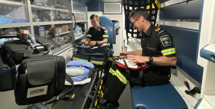 Paramedics sitting inside an Ambulance examining equipment
