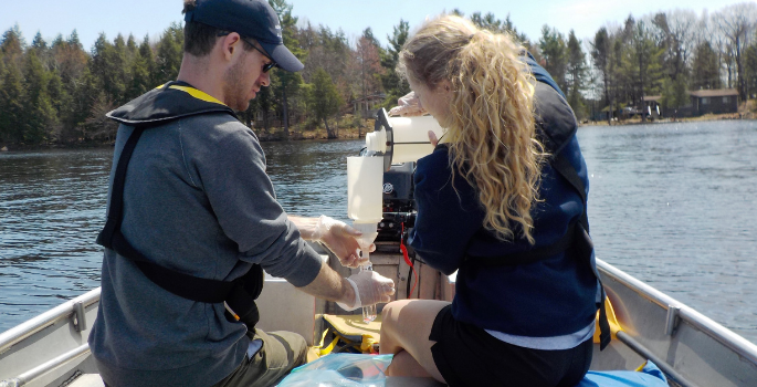 Two summer students conducting water testing