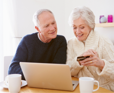 An elderly couple sits at a table with a laptop and are viewing a cellphone