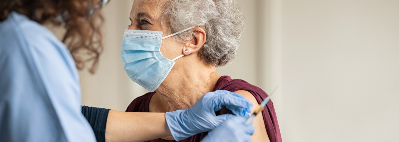 a senior reciving a vaccination in the arm