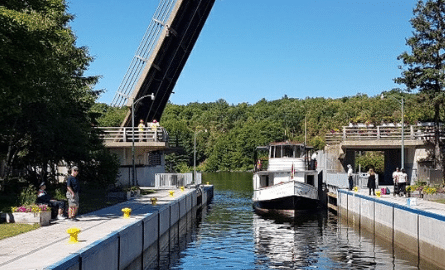 port carling locks with people walking on docks and a boat