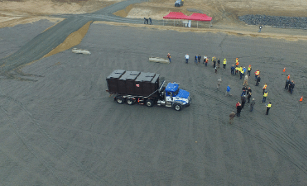 aerial view of landfill open cell with truck and group of people