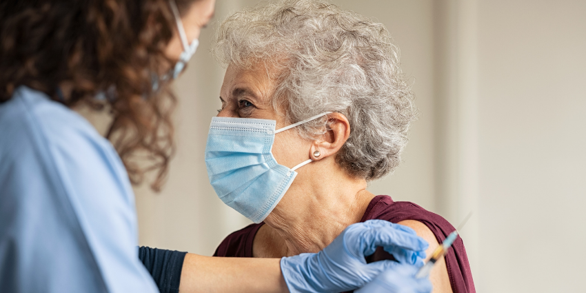 a senior woman wearing a mask getting a vaccination from a woman in a blue uniform