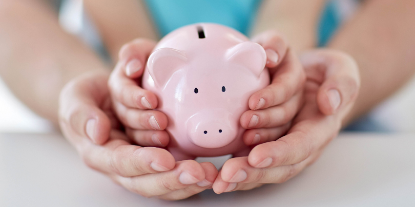a pink piggy bank in the hands of a child which are held by hands of an adult
