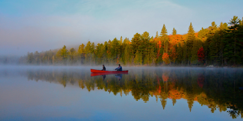 two people fishing in a red canoe on a lake in the fall