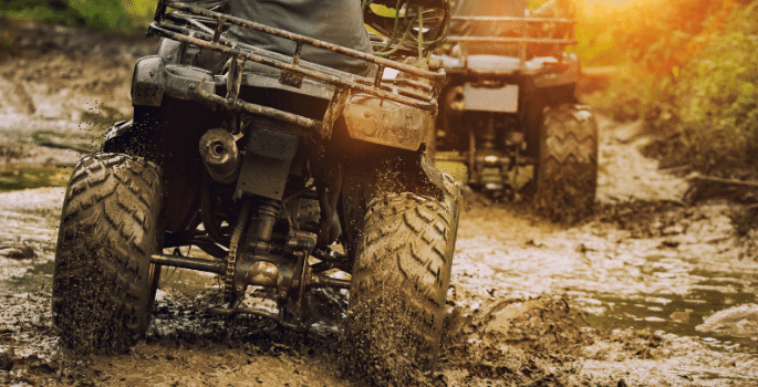 all terrain vehicles driving through the mud